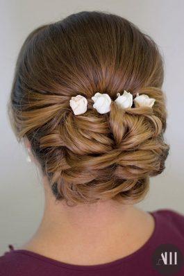 Аккуратный низкий пучок на свадьбу с украшением из роз