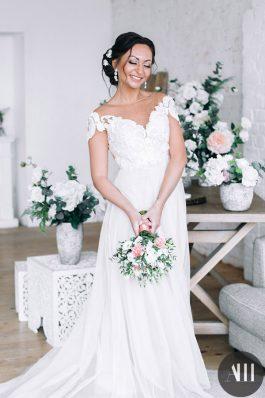 Прическа на свадьбу средний пучок с украшением и яркий макияж