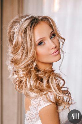 Объемная греческая коса набок с украшением и красивый макияж на свадьбу