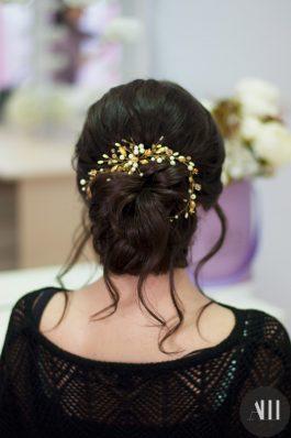 Плотный низкий пучок с выпущенными прядками и золотым украшением