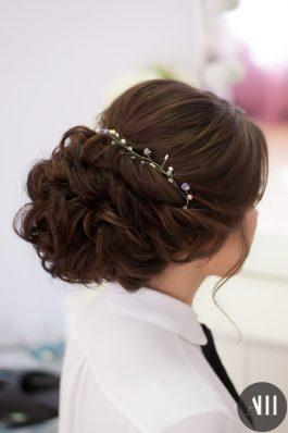 Свадебная прическа пышный низкий пучок украшенный веточкой