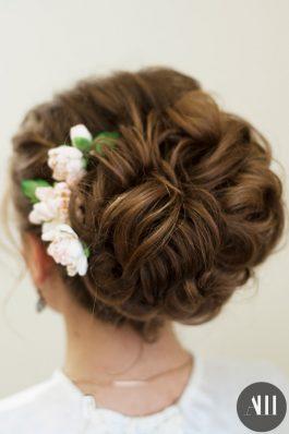 Воздушный пучок на свадьбу с цветами на средние волосы