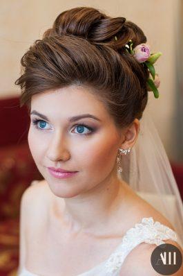 Высокий пучок на свадьбу с цветами и фатой